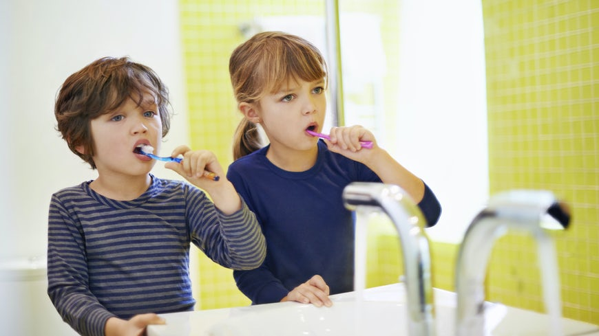 Two young children cleaning teeth
