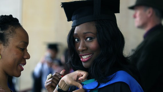 Female graduand smiling at the camera. She's wearing a black graduation cap and gown.
