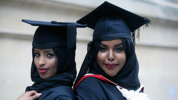 Two female graduands standing back to back and smiling into the camera.