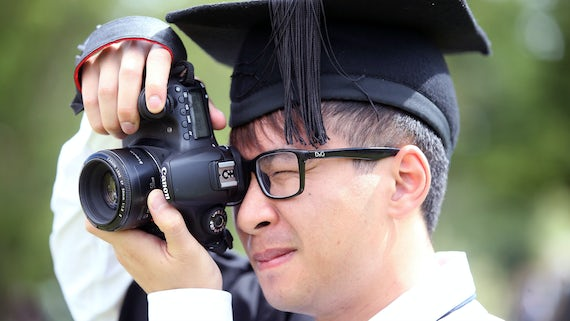 Close up of a male graduand taking a photo with a Canon DSLR.
