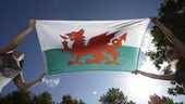 Welsh flag behind held by two people
