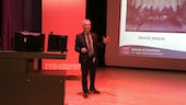 Professor Mike Lewis standing in front of screen, giving lecture
