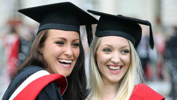 Two female students standing together smiling. Both are wearing black, white and red graduation gowns.