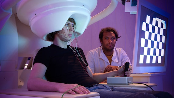 A researcher monitors a participant who is sitting in the MEG scanner