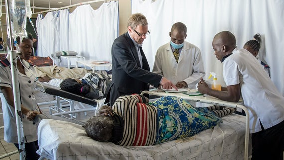 Dr Andrew Freedman talking to hospital staff in Northern Namibia, next to a hospital bed where a patient is lying.