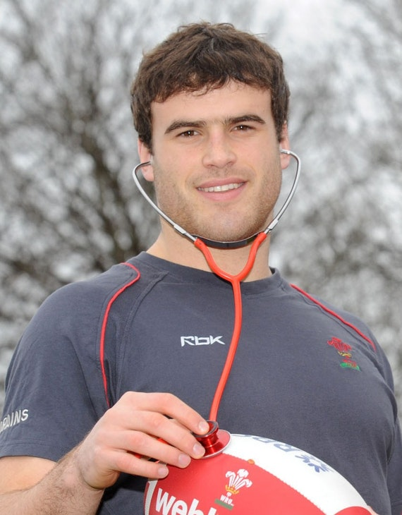 Photo of a man holding a stethoscope over a rugby ball