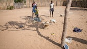 Family listening to a solar powered radio in a northern Namibia homestead