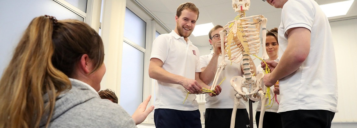 Physiotherapy students with skeleton model