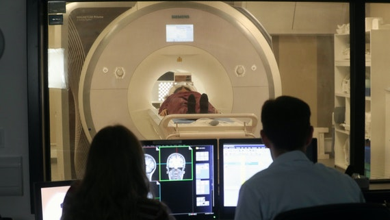 A participant lies in an MRI scanner while a male and female researcher operate the scanner