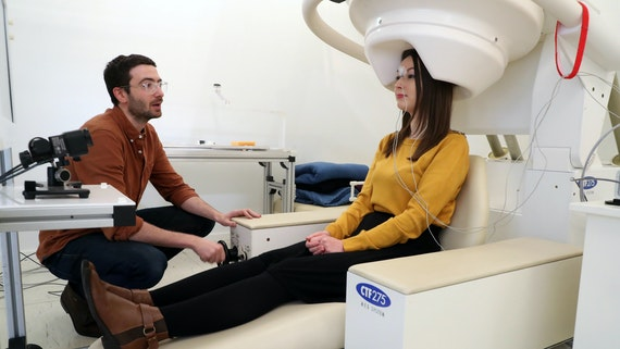 A female participant sits in a big white MEG scanner while a male researcher prepares the experiment
