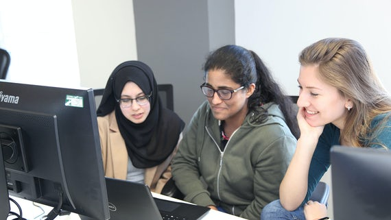 Three students sitting behind computeres