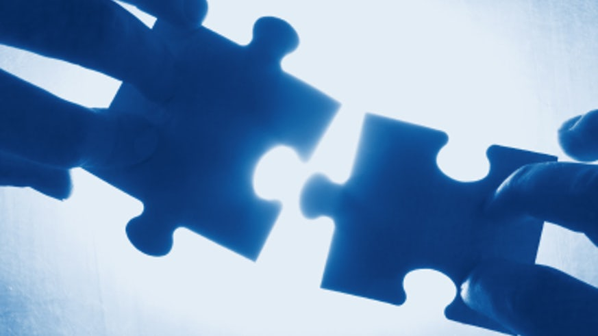Stock image of puzzle pieces being put back together