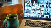 A laptop showing a zoom call with lots of people and a cup of tea on a table