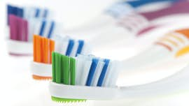 Row of differently coloured toothbrush heads.