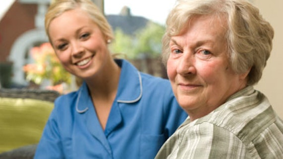 Elderly lady with female carer in blue uniform