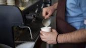 Barista pouring milk into espresso
