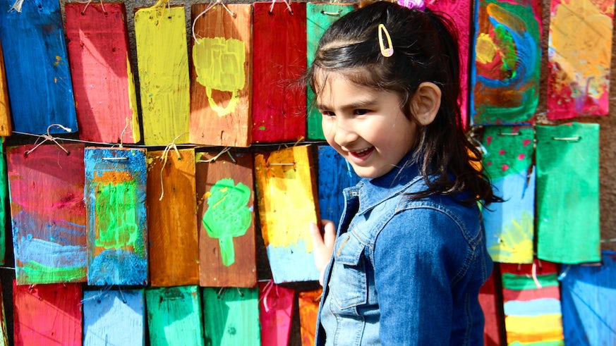 Young girl in front of colourful mural