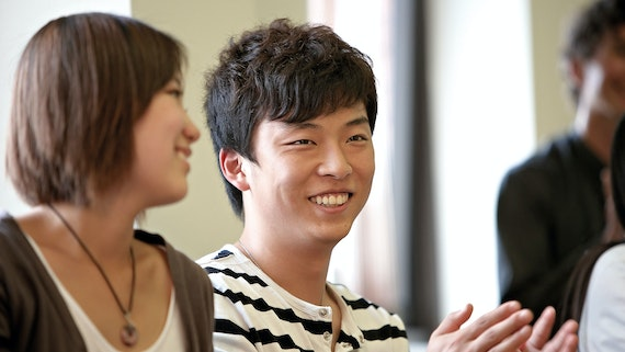 Male and female student chatting and smiling in seminar