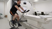 Photograph of a man on an exercise bike in front of an MRI scanner