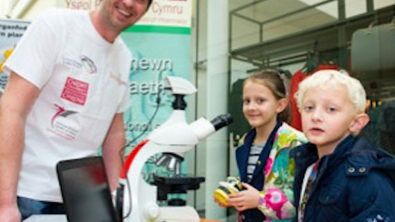 James Blaxland showing children the pollen in honey through a microscope during Environmental Day