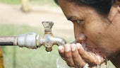 Indian woman drinking water from tap