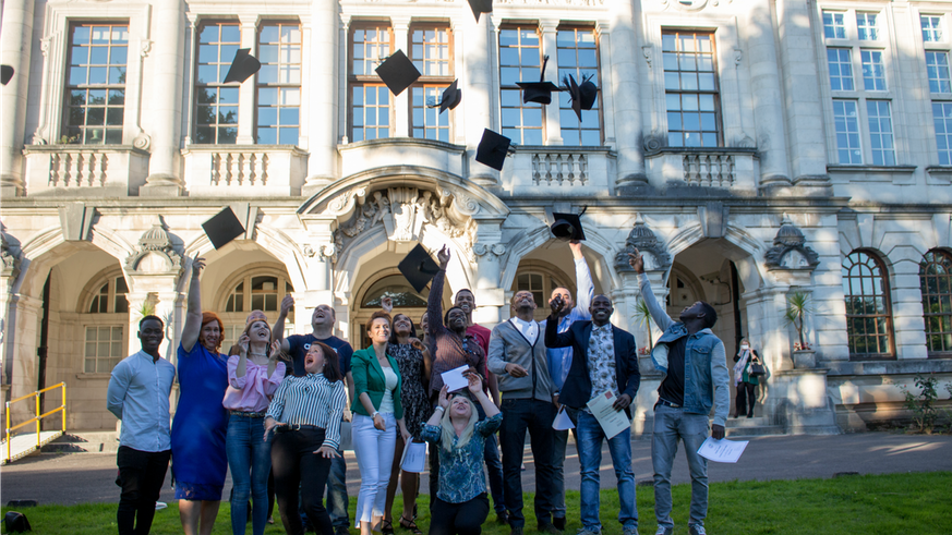 ASPIRE graduates throw hats in the air