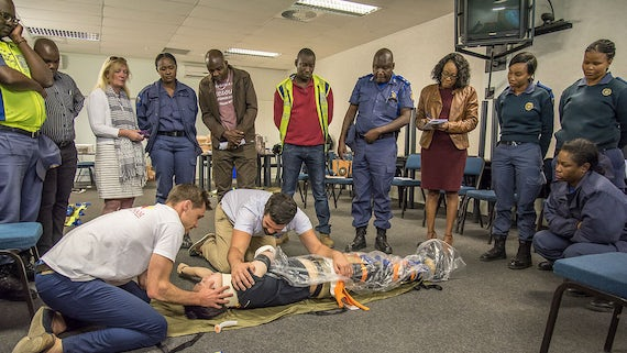 Two trainers kneeling on floor with a dummy model, watched attentively by police officers and others being trained