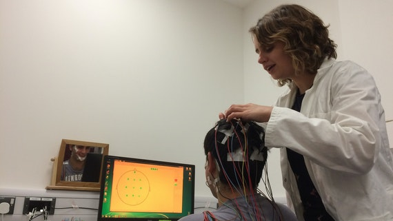 Young male participant gets EEG electrodes placed on head for sleep research experiment