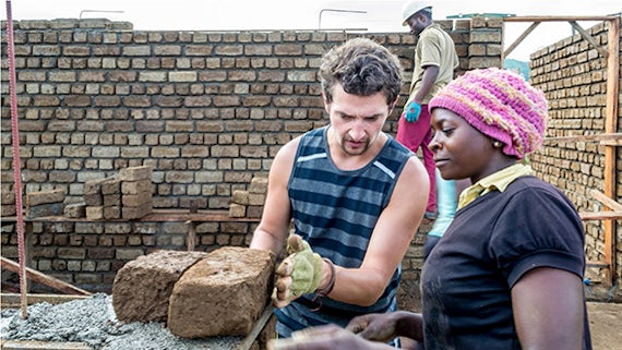 Student demonstrating construction techniques to a local woman