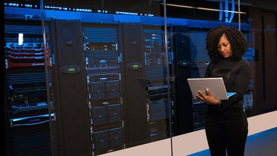 Woman at supercomputer holding a laptop