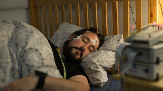 Male participant sleeping in sleep lab bed