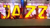 Lit up Jazz sign with performers