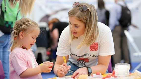 Woman and a little girl doing an activity at the Cardiff University stand at a Welsh festival