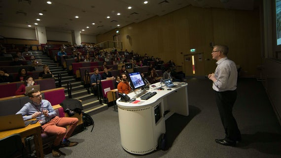 An audience of neuroscience researchers sit in a lecture theatre while a speaker gives a talk at the front of the room