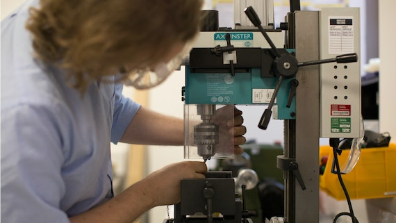a technical expert uses specialist machinery in the CUBRIC workshop