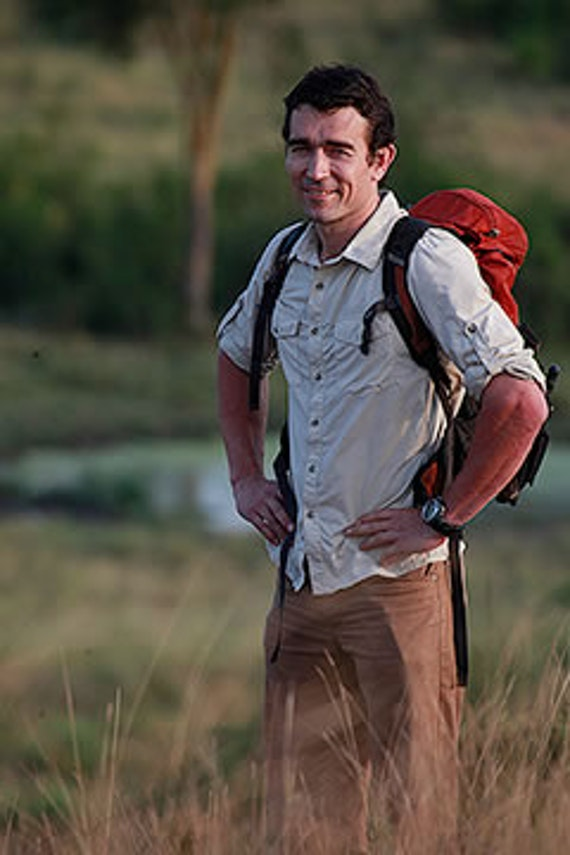Man standing in a field with his hands on his hips and smiling into the camera.