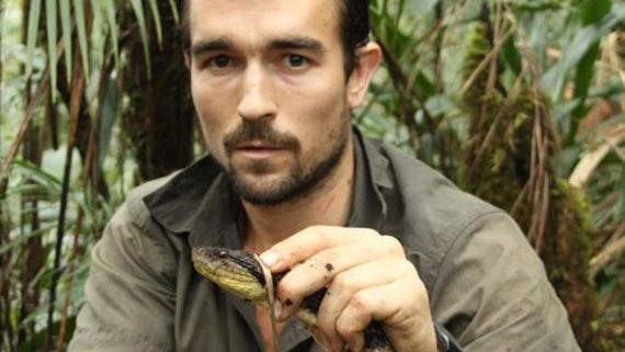 Man in the jungle holding the neck of a snake.