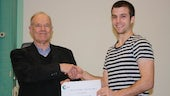 Two men shaking hands and holding a certificate.