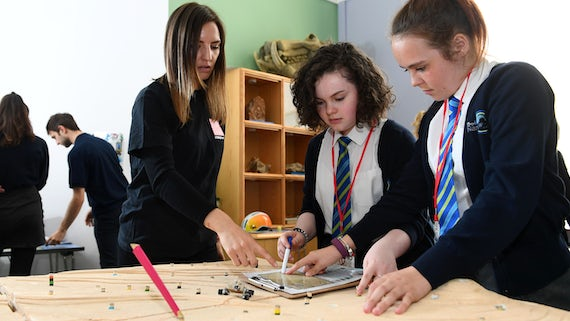 Two female pupils take part in a science activity lead by a female Cardiff University volunteer in the National Museum Cardiff
