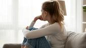 Teenage girl sat on sofa