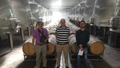 Three men in wine production facility