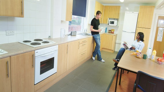Kitchen area with two people talking, one seated, the other leaning against cabinet.