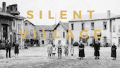 Black and white image of ten people (men, women and children) standing in a row, in the middle of a village, and facing the camera straight ahead.