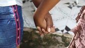 A Real Choices, Real Lives study participant holds hands with her mother. Photo credit: Plan International Dominican Republic.