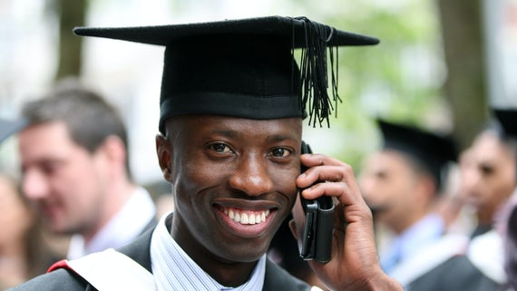 Male student talking on a mobile phone. He's smiling and wearing a black graduation cap and gown.