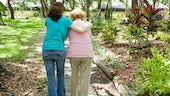 Elderly lady walking with carer in park setting