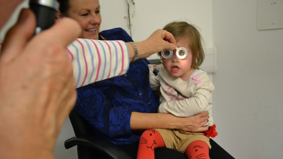 A child with Down's Syndrome having an eye test.