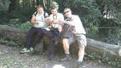 Three men sitting on tree trunk