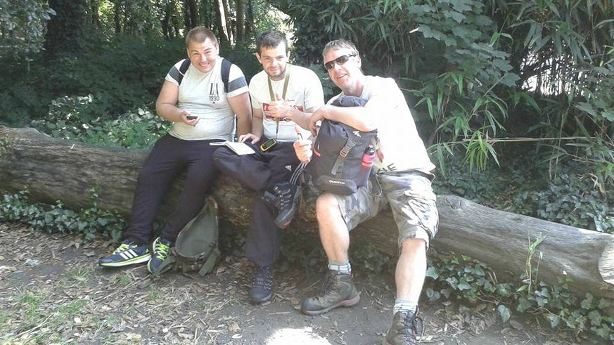 Three men sitting on tree trunk