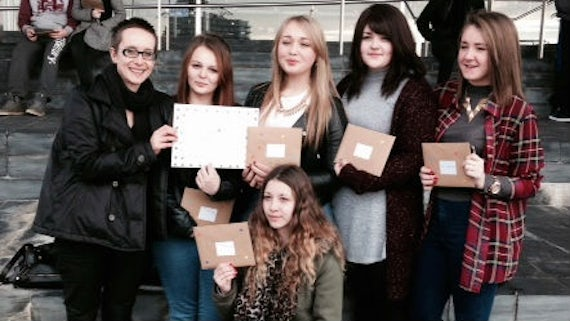 Female students standing outside the Senedd in Cardiff Bay, holding Valentine cards for an anti-abuse campaign